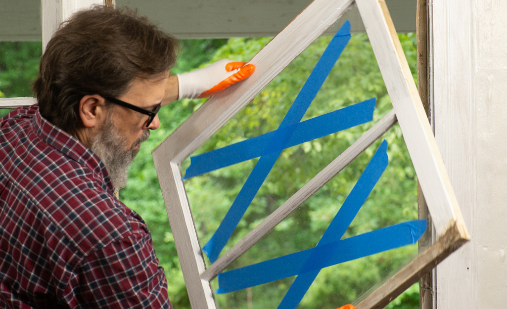 Man removing an old window with two blue taped Xs.