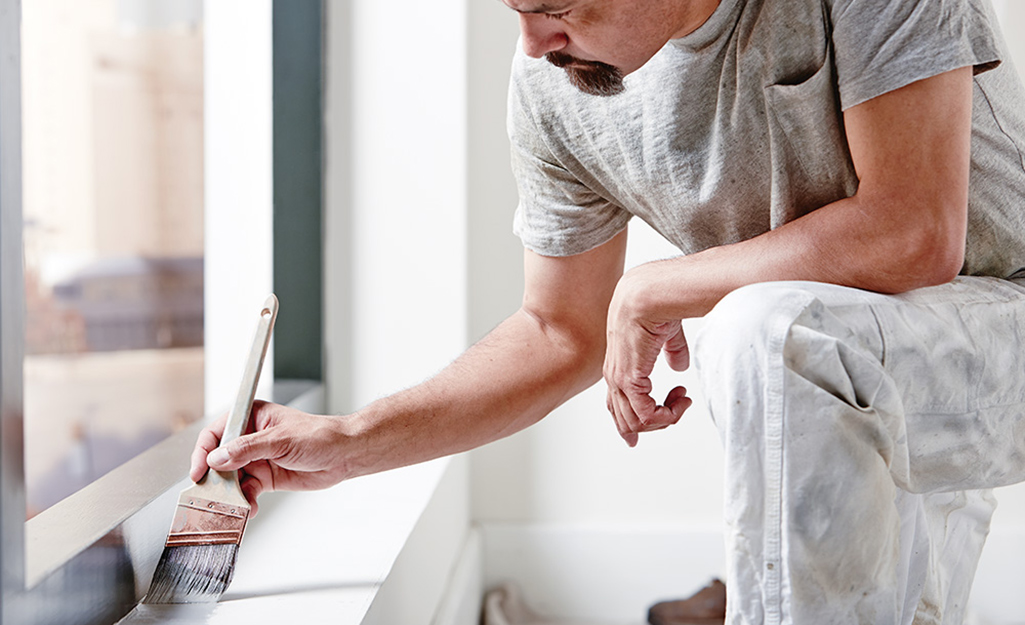 A man paints a window sill indoors.