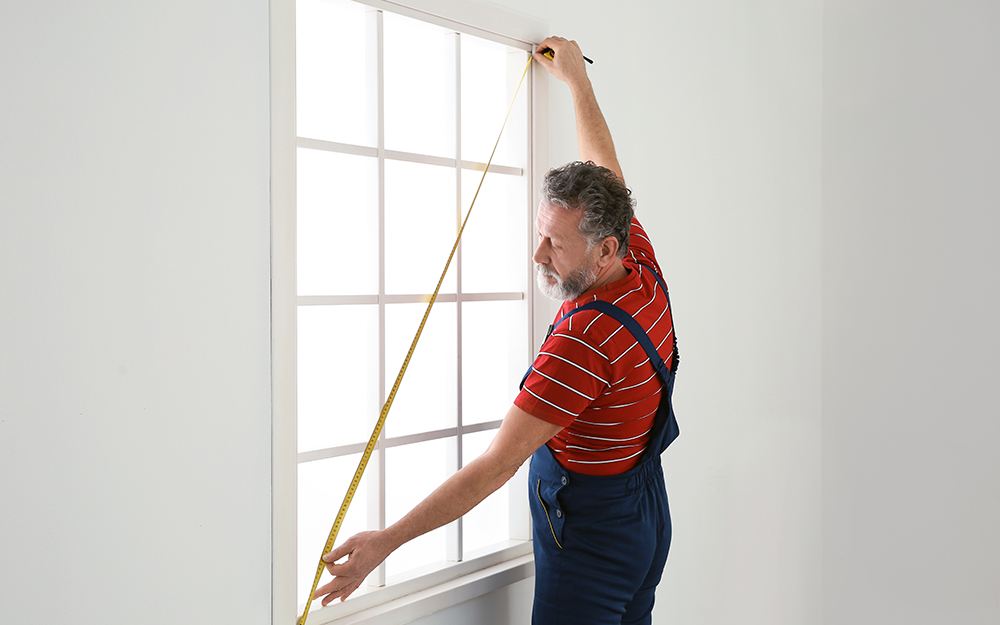 Man double checks that the window is square using a tape measure.