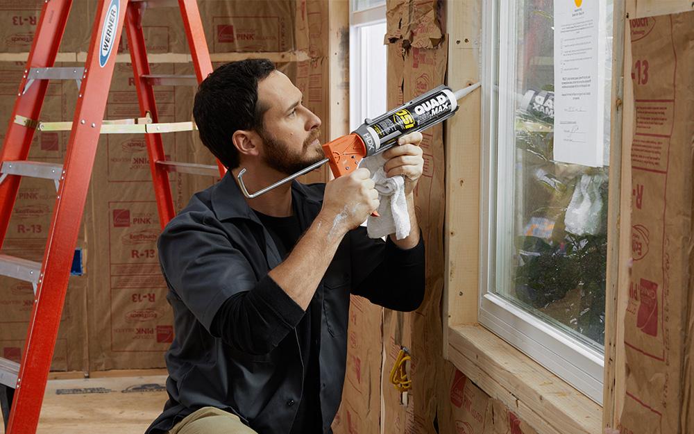 Man applies caulk along the window frame.