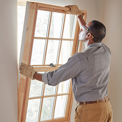 Man wearing protective eyewear while installing wooden frame window from inside a house.