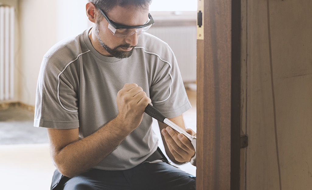 Man wearing safety glasses working to pry a door free of its frame.