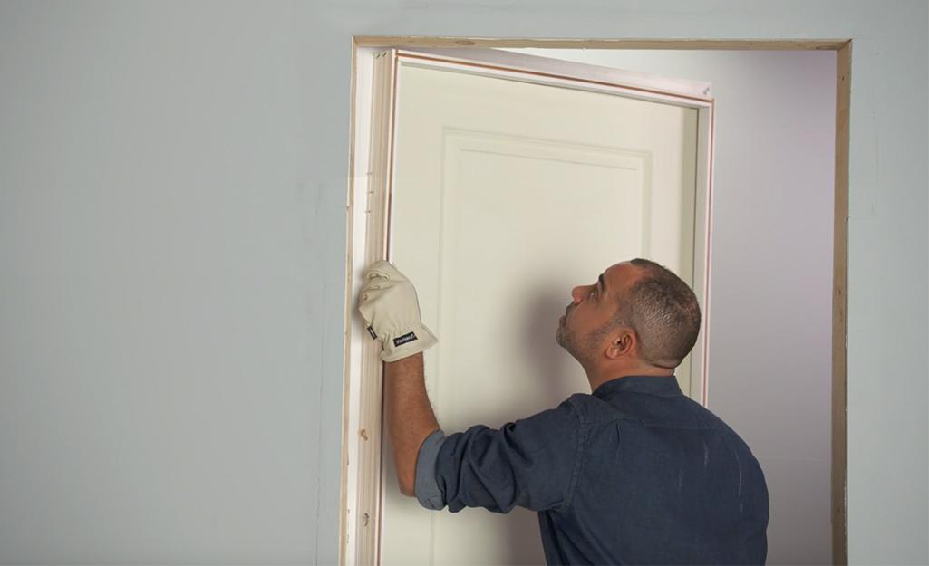 A man positioning a prehung door in a doorway.