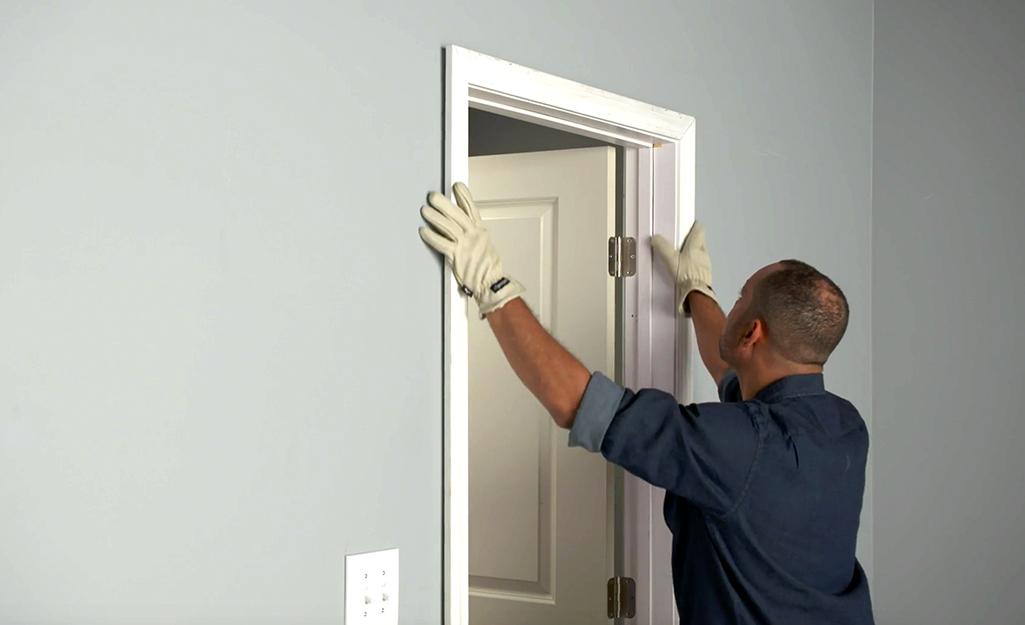 A man positioning door trim to a door.