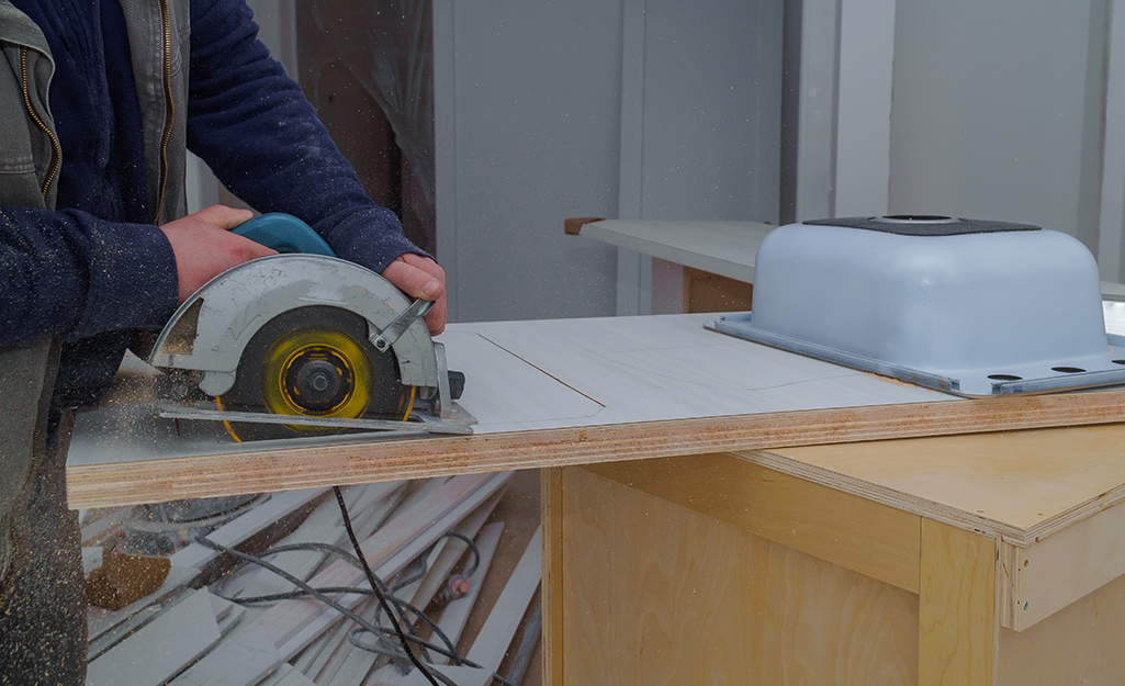 A person uses a circular saw to cut a sink hole in a countertop.