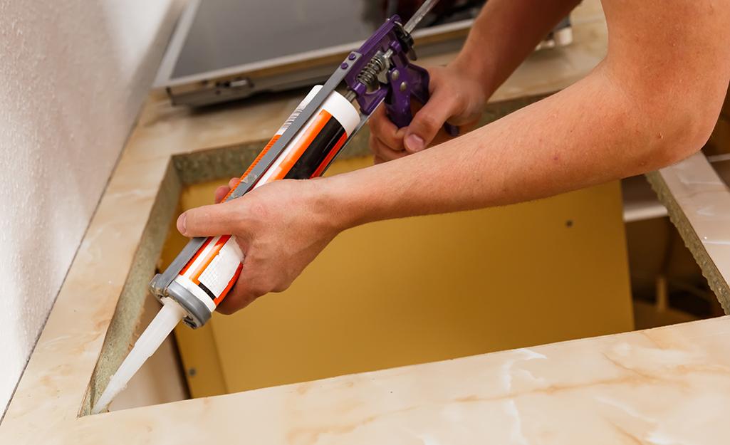 A person use a caulk gun to apply caulk around the edge of a countertop sink hole.
