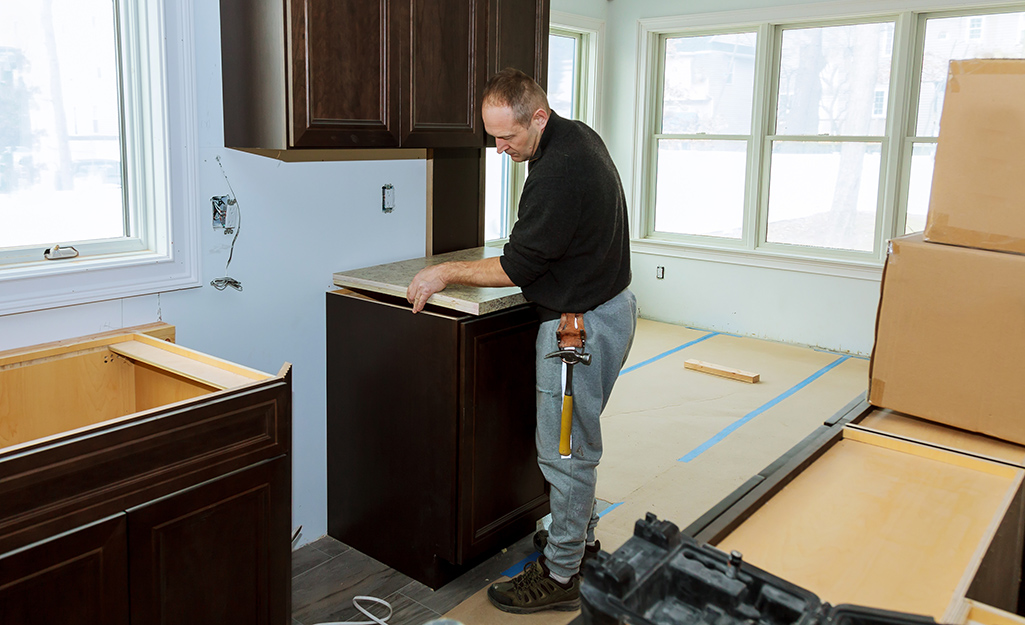 A man installs base cabinets in a kitchen.