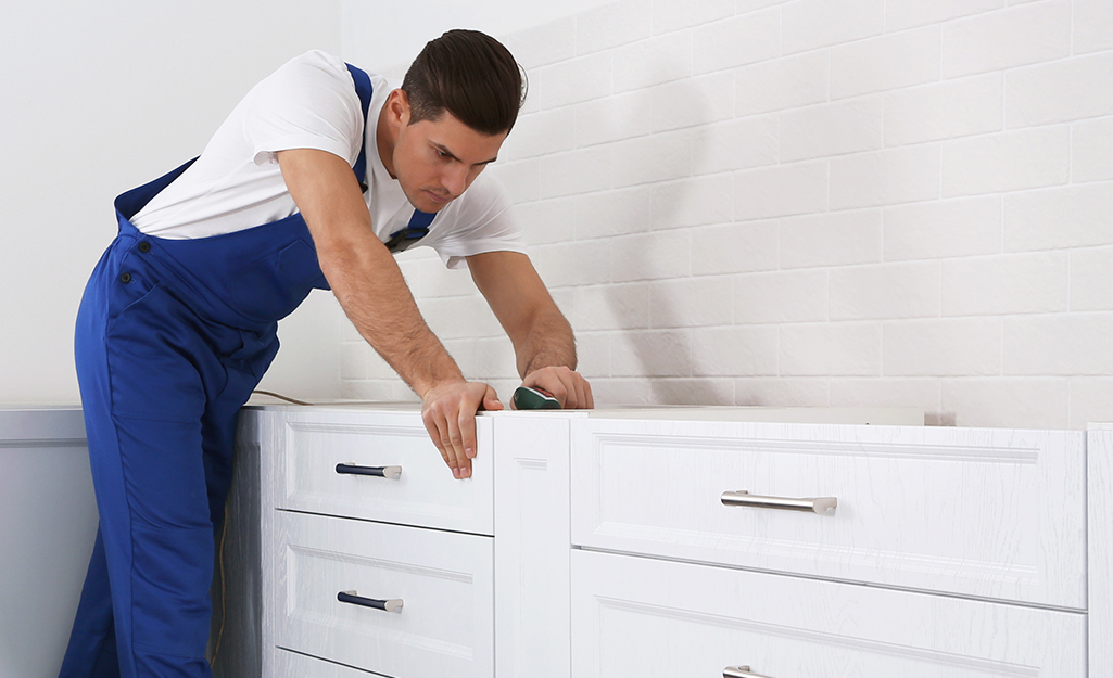 Man sets neighboring cabinets in place.