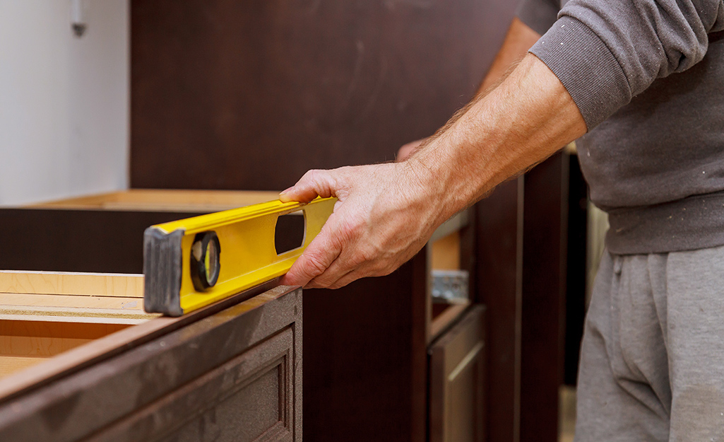 Man uses level to make sure cabinets are level and plumb.