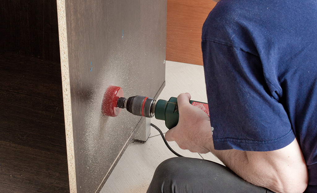 Man uses drill to cut wiring.