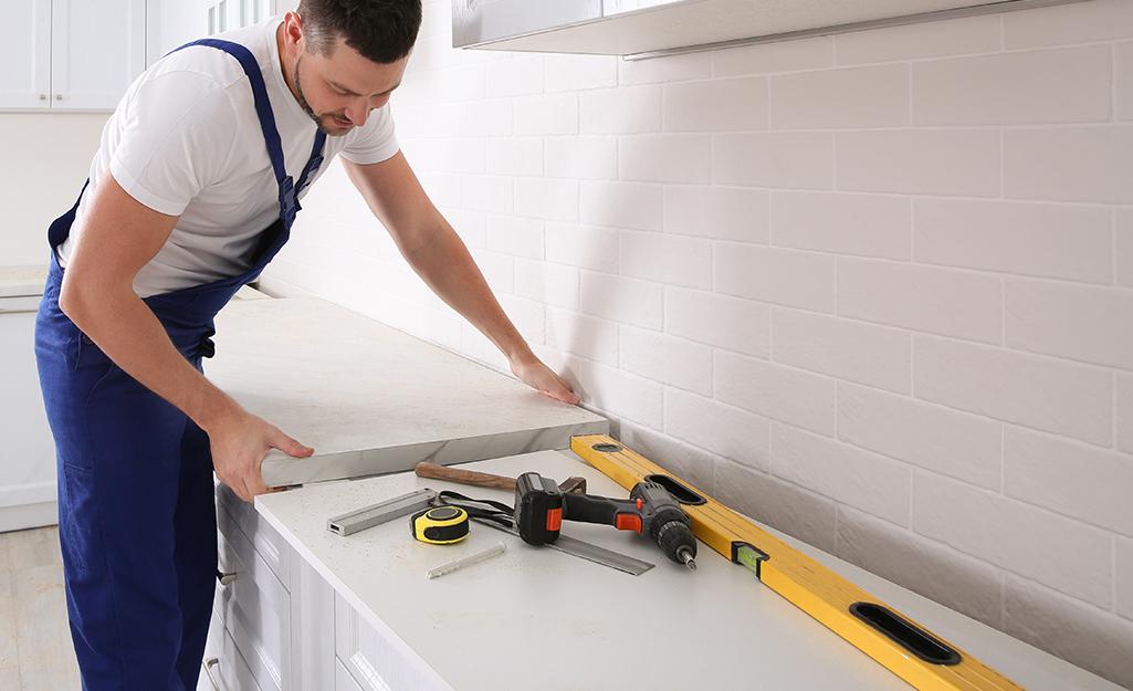 A man installs cabinets.