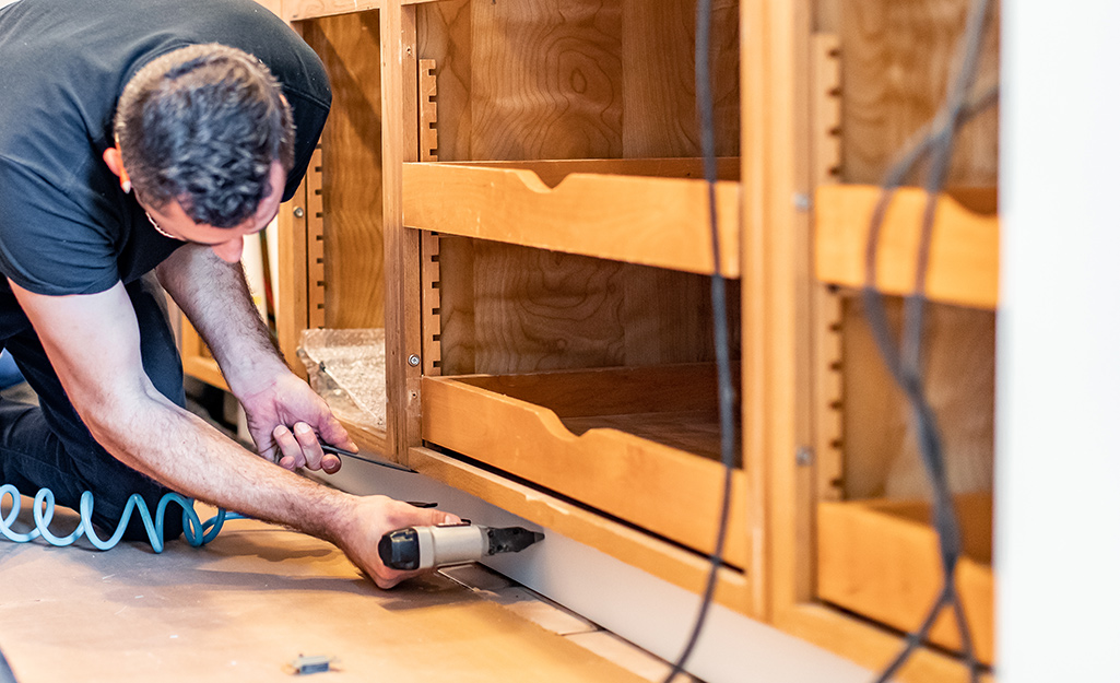 A man installs a toe-kick to the bottom gap of a cabinet.
