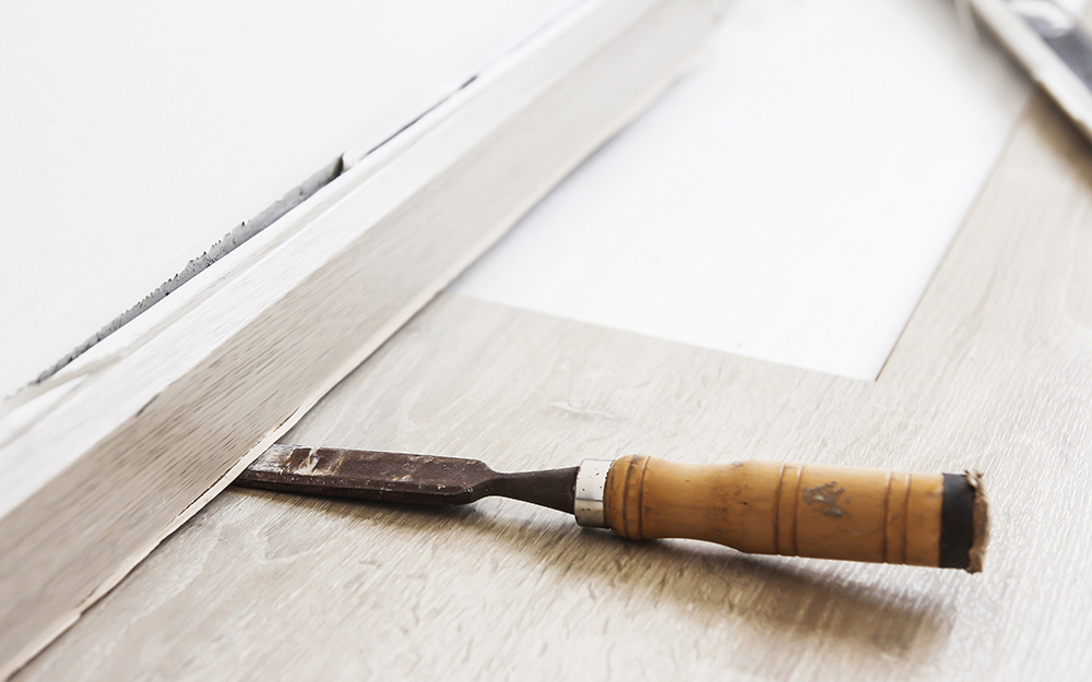 A chisel is used to pry off old baseboard.