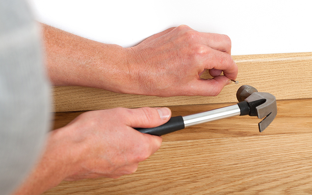 Person uses a hammer to install baseboard.