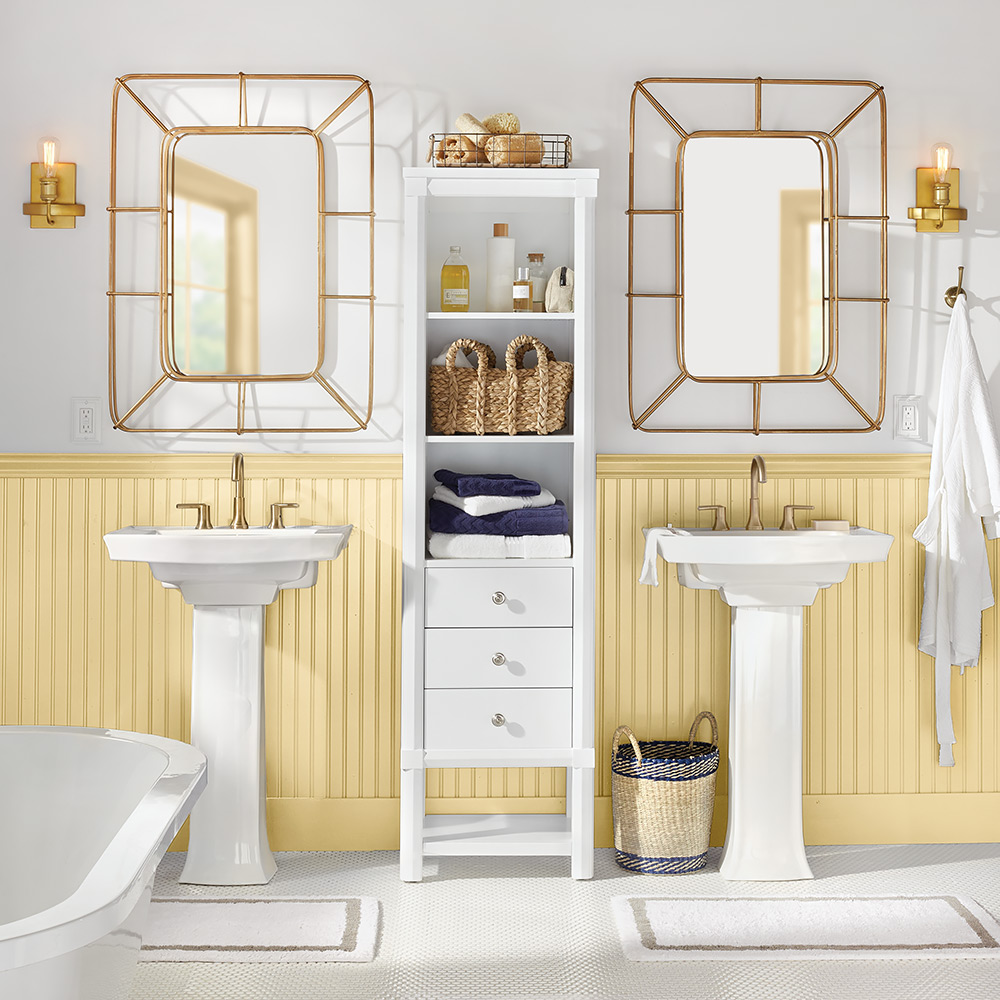 A bathroom with two sinks and headboard wainscoting painted yellow.