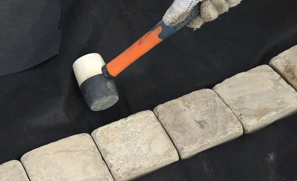 Someone using a mallet to align concrete bricks to edge a bed.