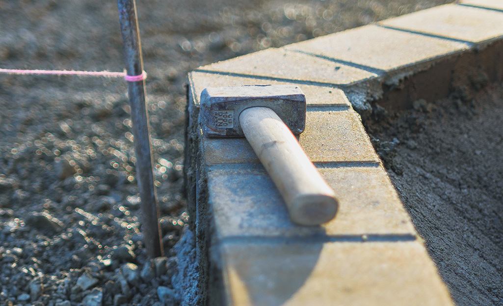 A sledgehammer sitting on top of a row of brick edging around a garden bed.