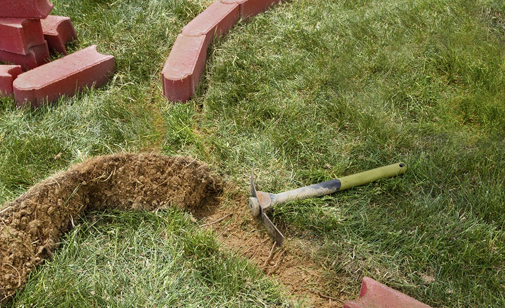 Someone using a mattock to make a curve in the lawn to install brick edging.