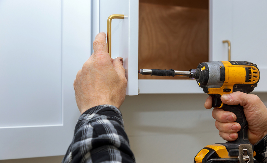 A person using a power drill to remove cabinet handles.