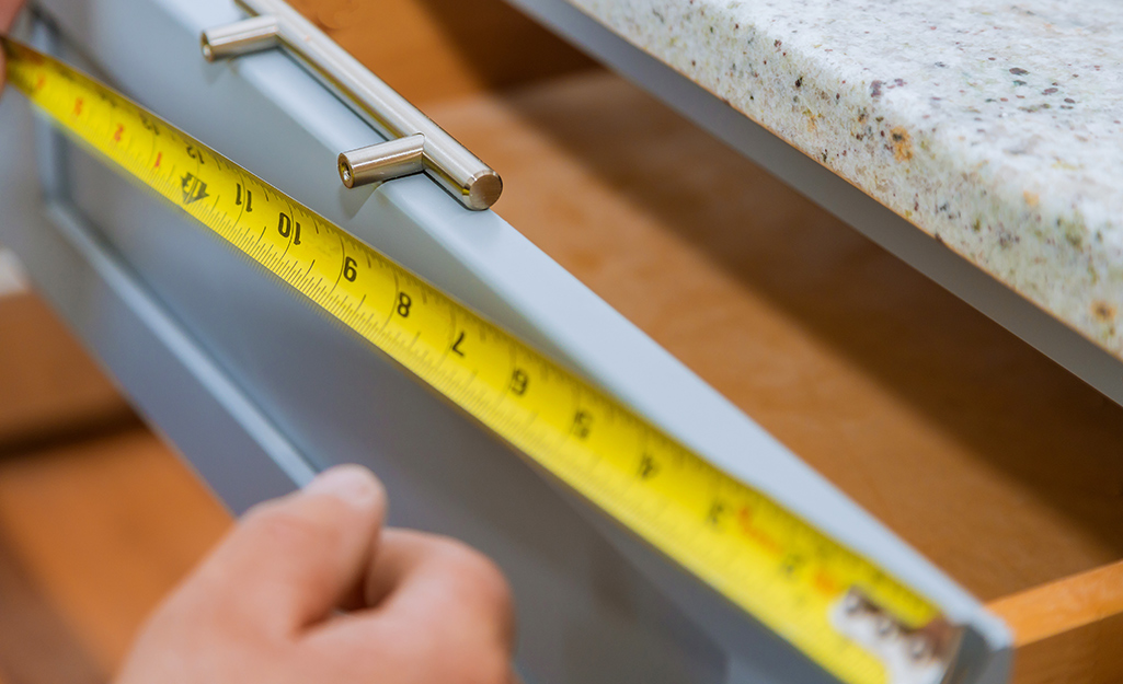 A person measuring a cabinet drawer.