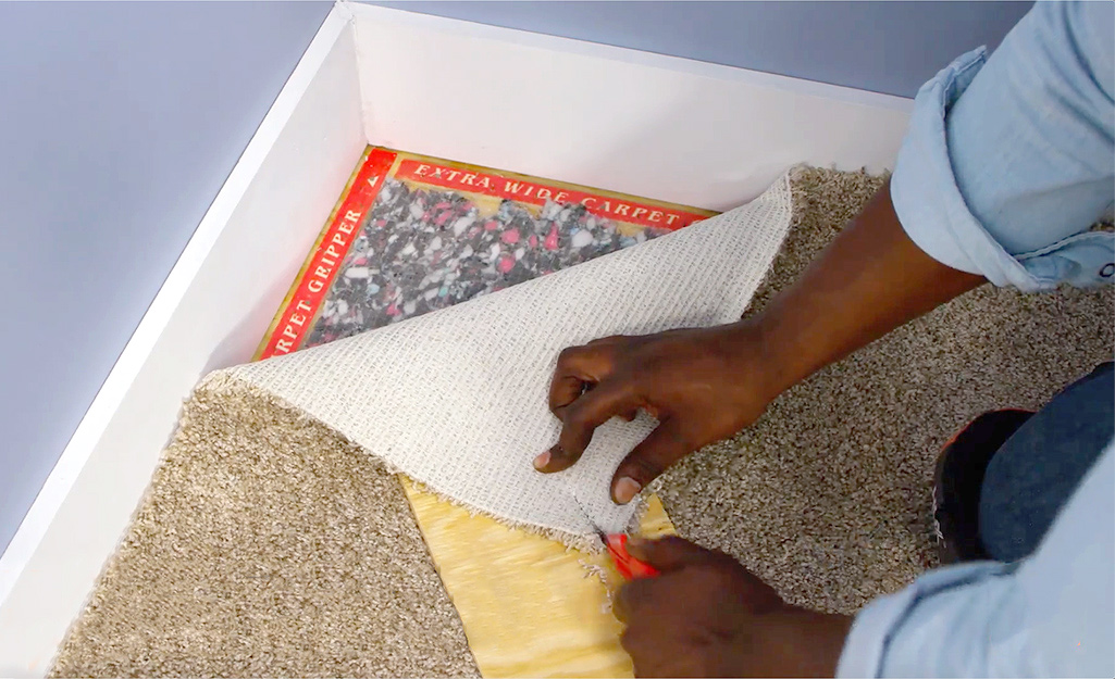 A person making a relief cut in the corner of carpet to be installed.