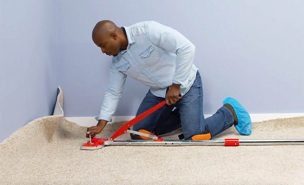 A person using a power stretcher for carpet installation.
