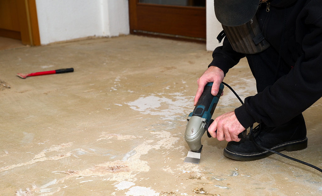 A man wearing a safety mask uses a sander to prepare a subfloor.