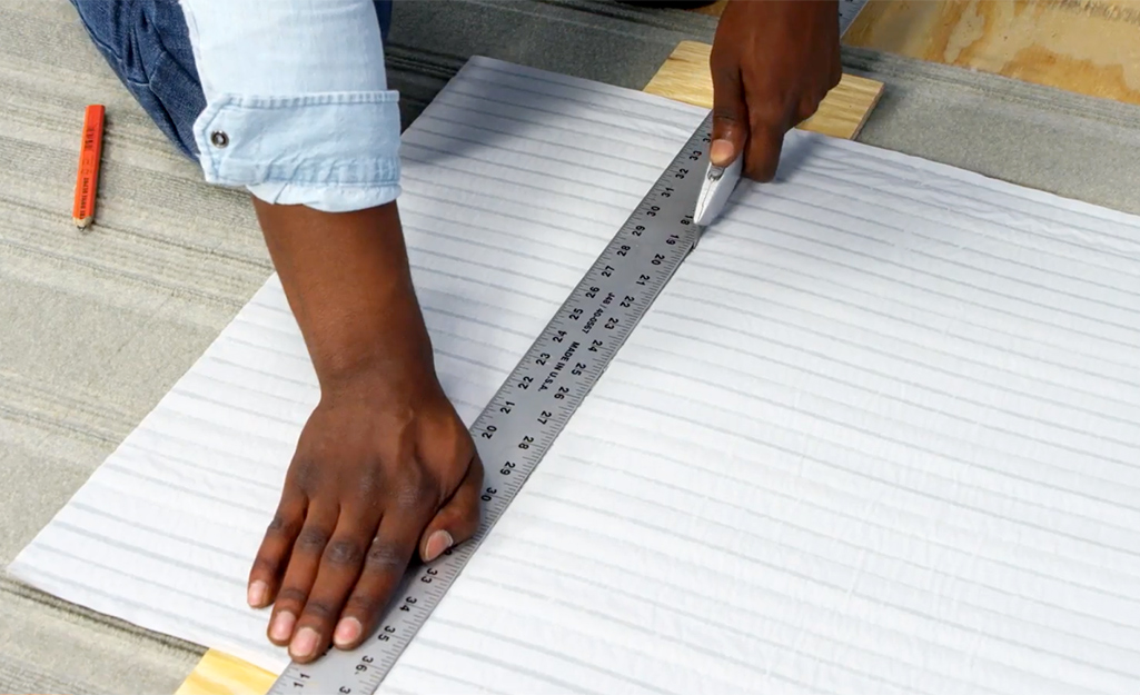 Man trims carpet tile using a utility knife and a straight edge ruler.