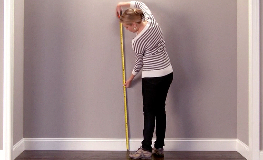 A woman uses tape measure to measure a wall in her closet.