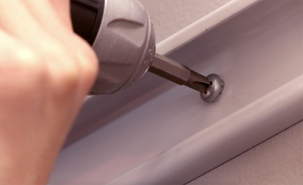A drill is used to attach closet shelving to a wall.