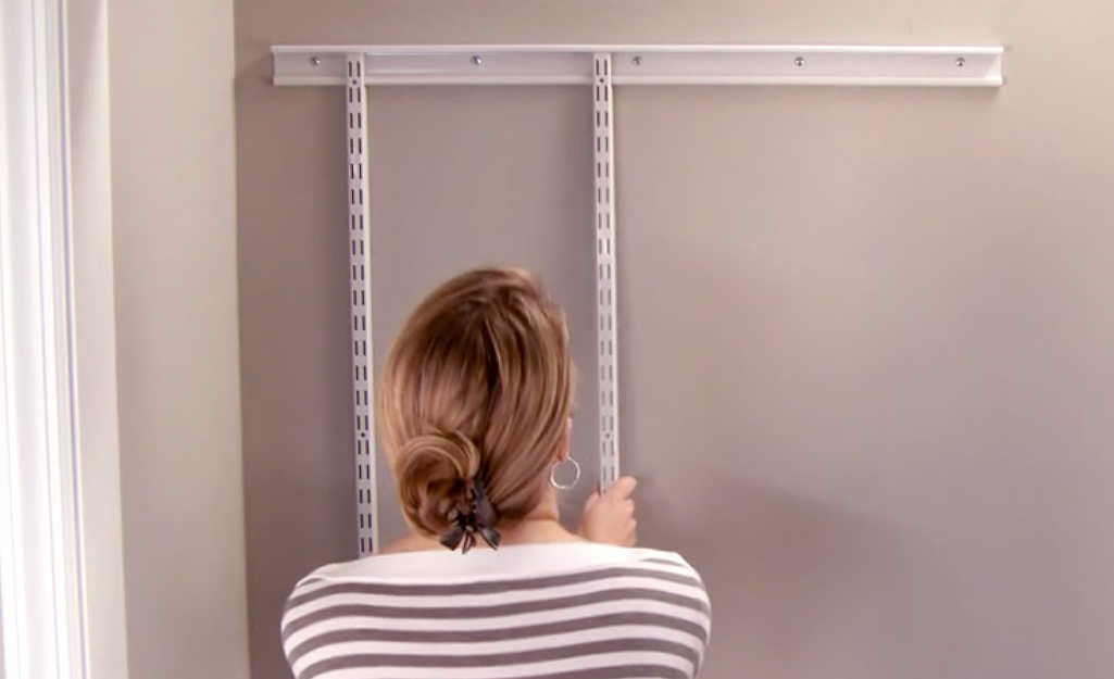 A woman installs uprights to a shelving system.