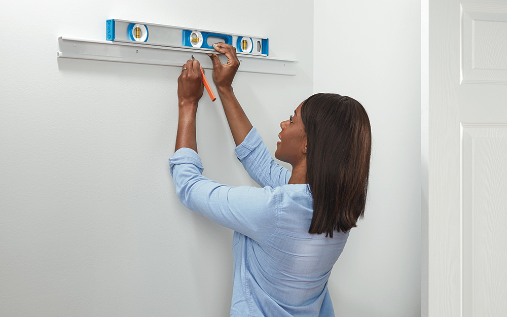 A woman leveling hang track of a ClosetMaid ShelfTrack closet storage system