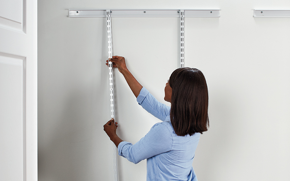 A woman installing ShelfTrack closet storage system standards