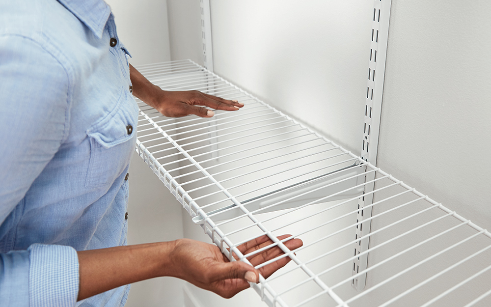 A person installing ClosetMaid ShelfTrack wire shelves