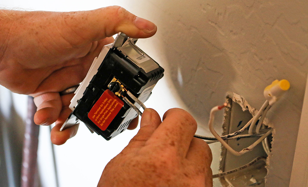 A man connects the new dimmer switch to the outlet.