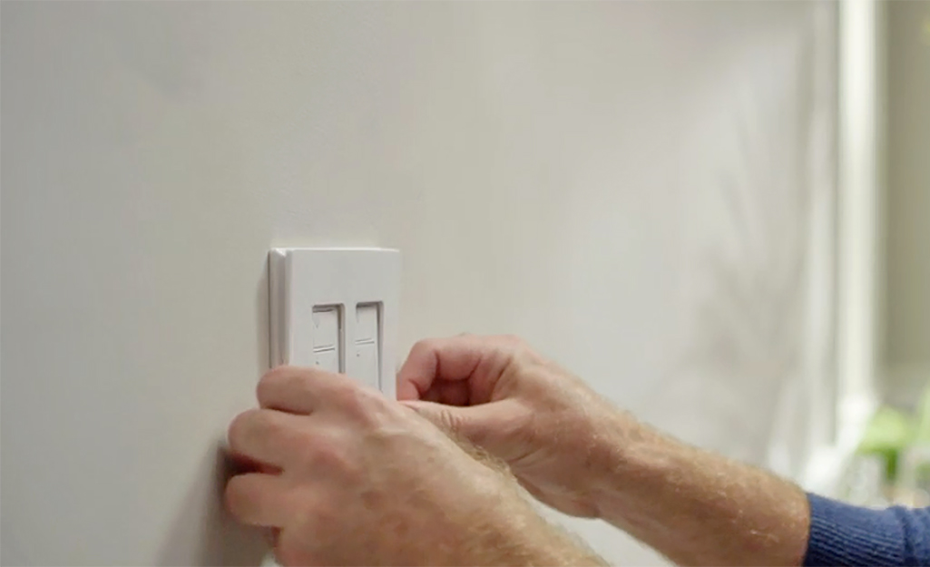 A person is mounting their new dimmer switch wall plate.