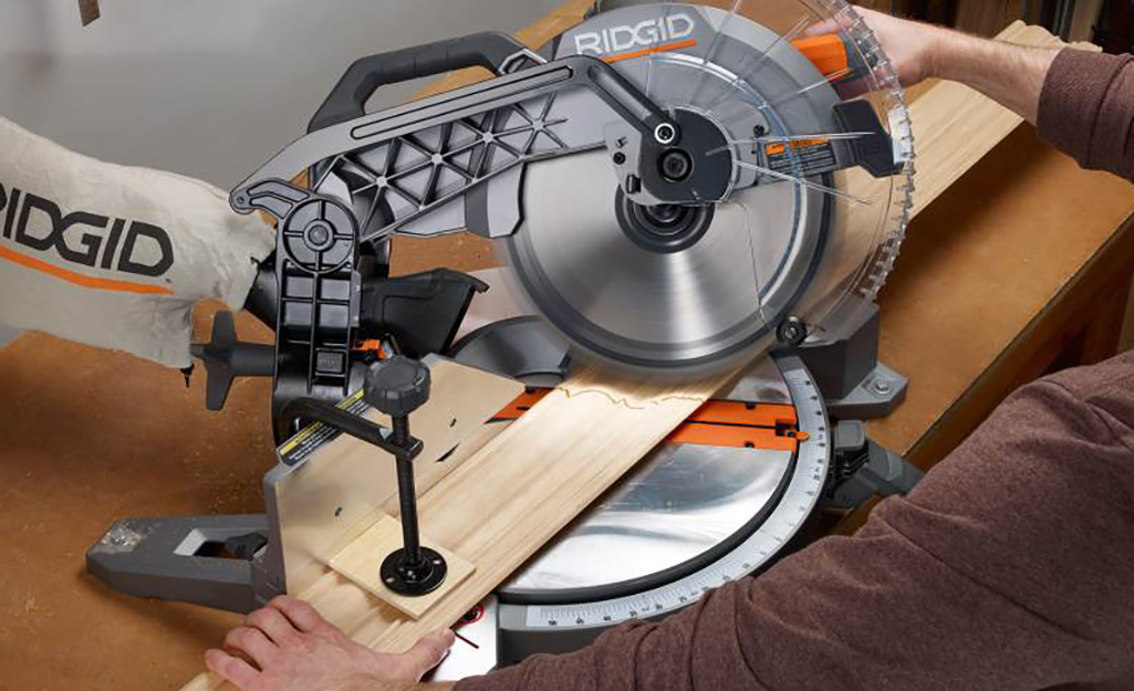 A person uses a saw to cut a piece of door trim.