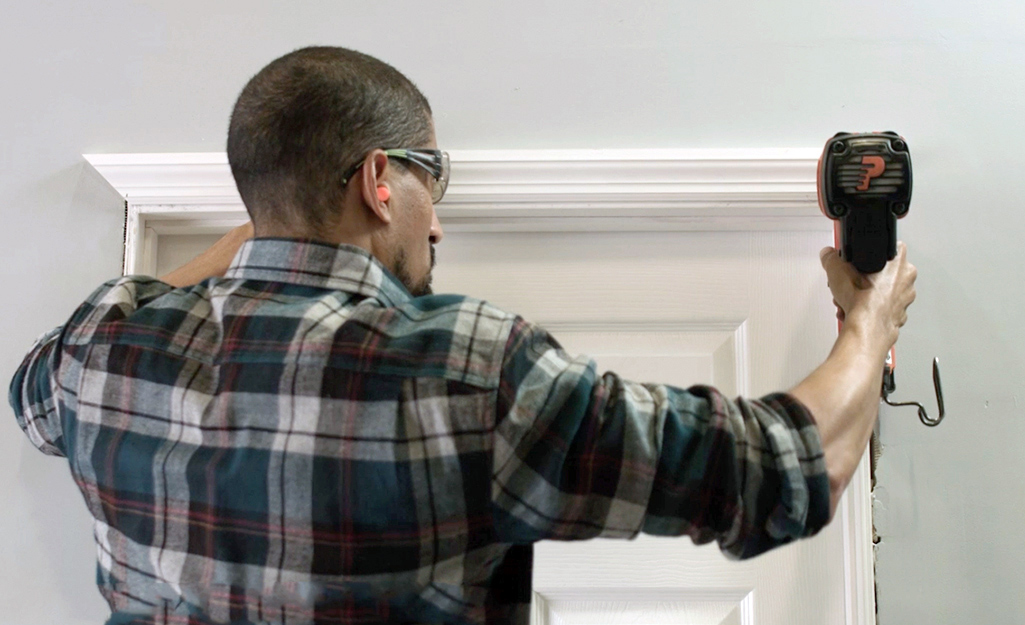 A person wearing ear plugs and safety glasses nails a piece of trim to the top of a doorway.