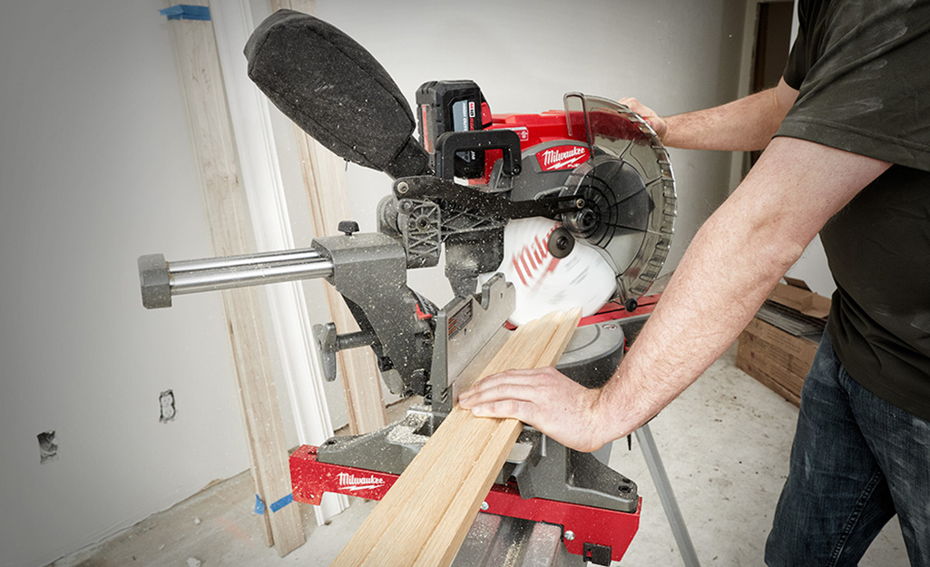 A person trims a piece of wood moulding with a miter saw.