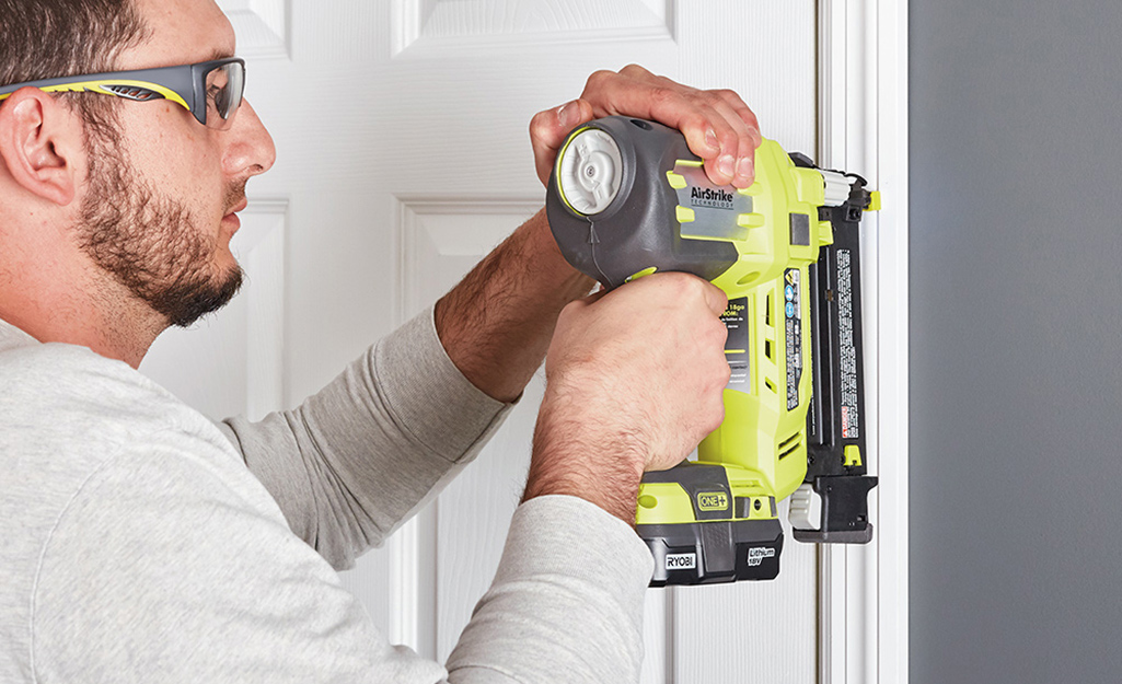 A person uses a nail gun to attach side trim to a doorway.