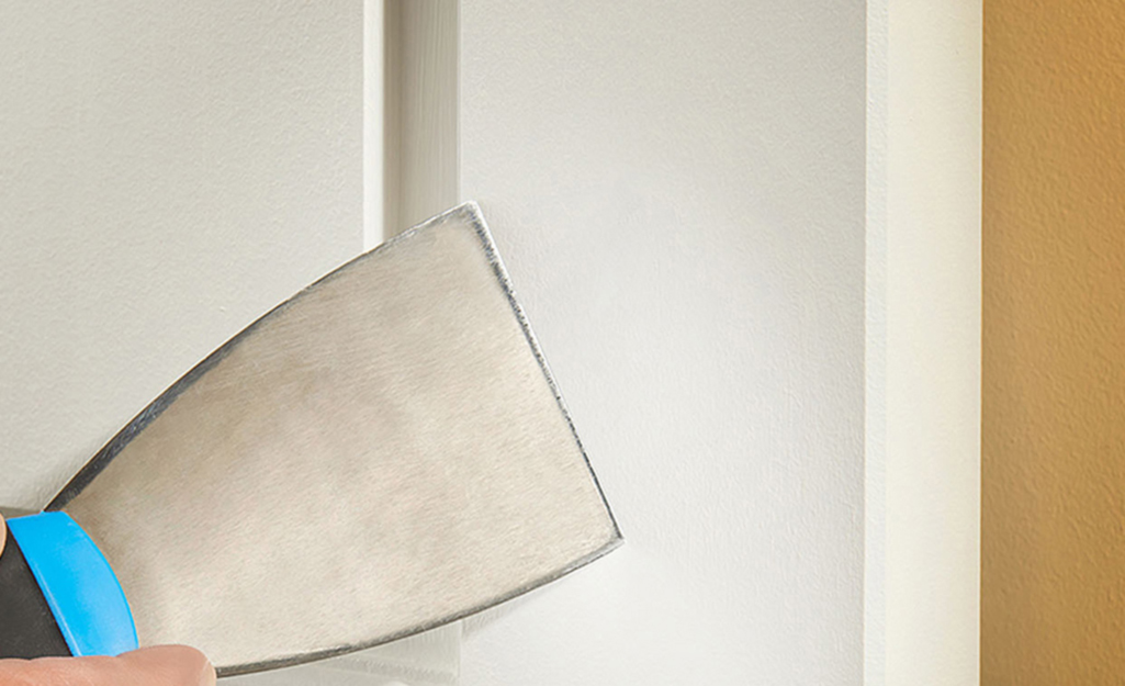A person uses a putty knife to smooth away excess spackling compound from door trim.