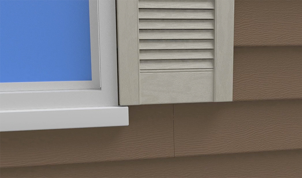 An exterior shutter is placed against a window for installation.