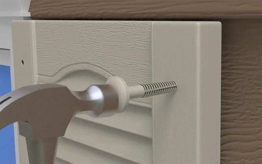 A hammer taps a shutter lock to install exterior shutters.