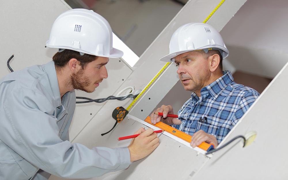men measuring glass block installation area