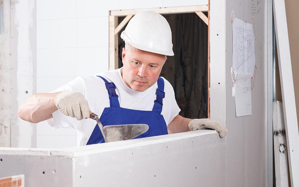 man applying mortar to wall surface