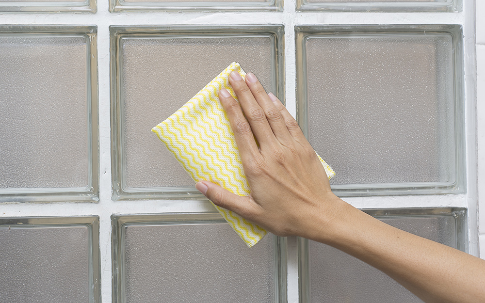 person cleaning glass block