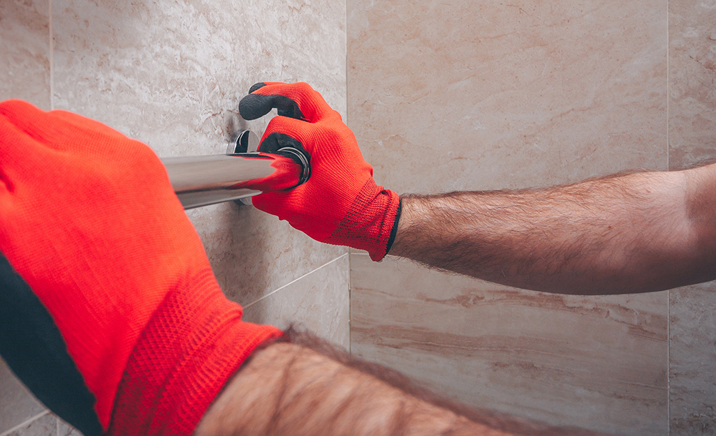 Person positioning the grab bar on the tile wall
