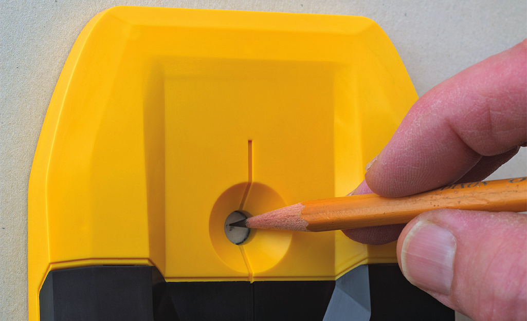 Using a pencil to mark the mounting hole