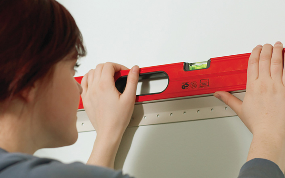 A level being used to mark the location for the top of base cabinets