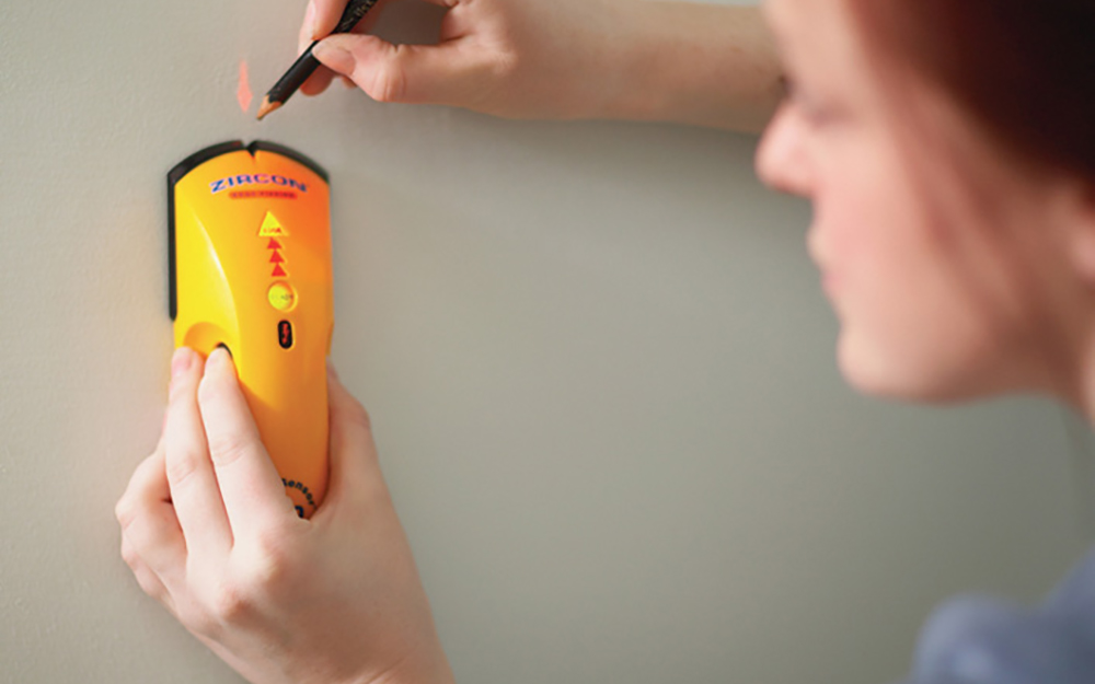A stud finder being used to locate studs in a wall